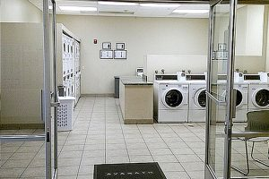 Castelar laundry room with several washers, dryers, and chairs